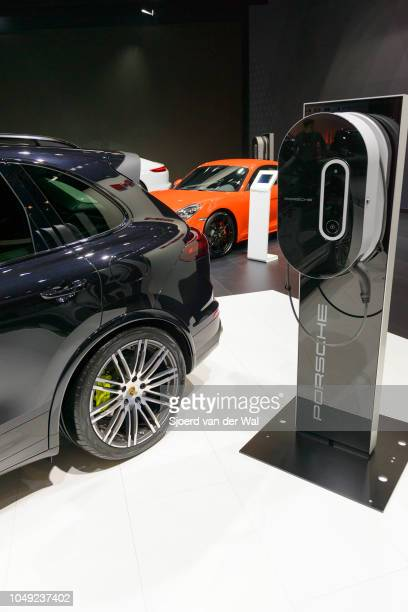 Porsche Cayenne S EHybrid charging port next to a Porsche Cayenne S EHybrid plugin hybrid luxury SUV on display at Brussels Expo on January 13 2017...