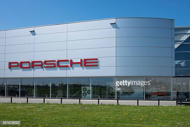 porsche dealership building with the porsche sign - asia carrera stock photos and pictures