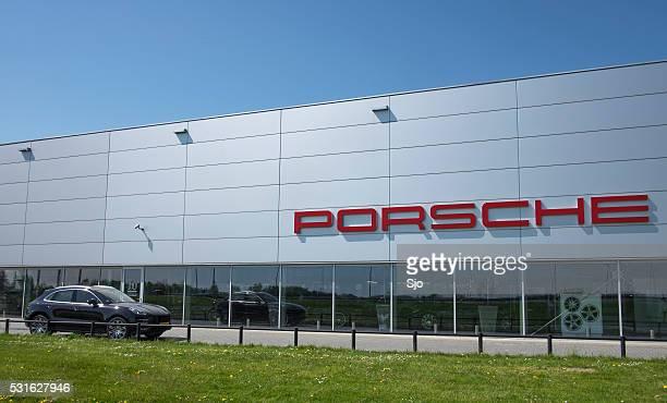 porsche dealership with a porsche macan suv - asia carrera stock photos and pictures