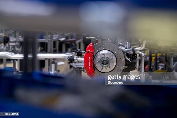 A Porsche logo sits on the brake caliper before being fitted to a Porsche 911 luxury automobile on the production line inside the Porsche AG factory...