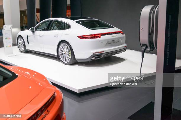 Porsche Panamera 4 e-hybrid luxury 4 door saloon performance car rear view and electric vehicle charging station on display at Brussels Expo on...
