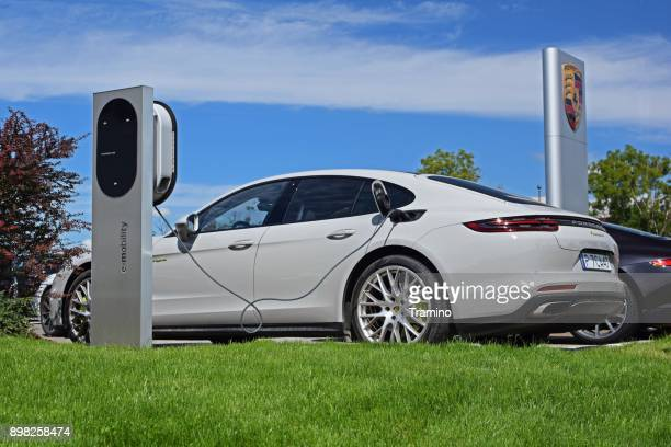 porsche panamera on the electric charging station - hybrid vehicle stock photos and pictures