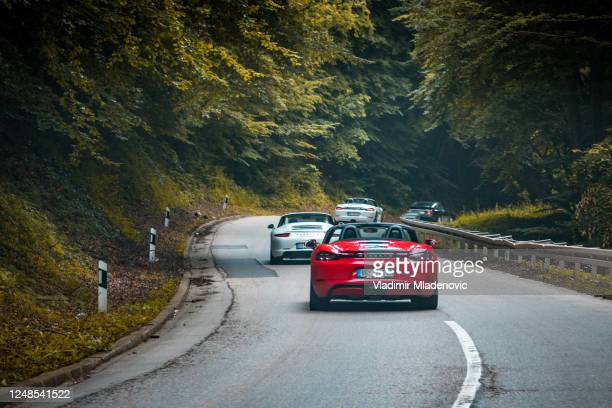 porsches driving in the group - porsche stock pictures, royalty-free photos & images
