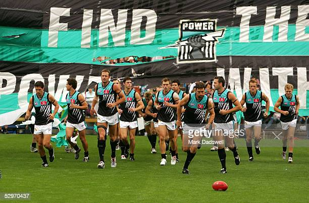 Port Adelaide Power run through the team banner before the AFL round three match between the Adelaide Crows and the Port Adelaide Power at AAMI...
