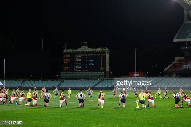 Port Adelaide Power, the Adelaide Crows and umpires take a knee in support of the Black Lives Matter movement before the round 2 AFL match between...