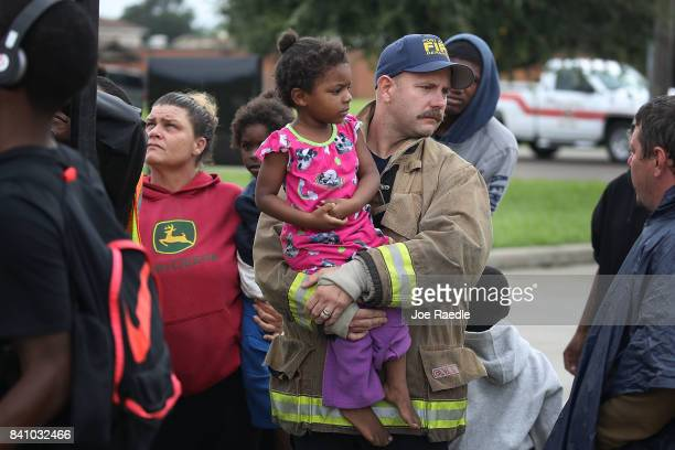 Port Arthur fireman holds an evacuee after she was rescued from the flooding of Hurricane Harvey on August 30 2017 in Port Arthur Texas Harvey which...