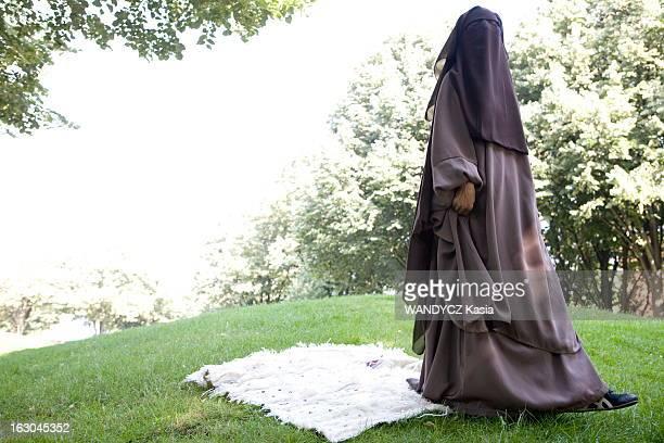 Port Of Burqa In France Nawel voilée de la tête au pied posant dans un parc de SAINTOUEN