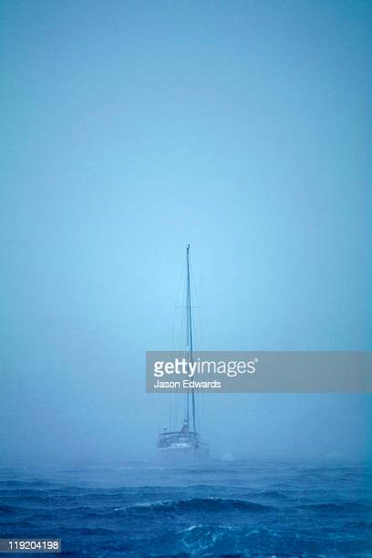 A tropical storm engulfs an ocean yacht with gale force wind and rain.