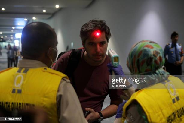 Port quarantine officers checks body temperature of passengers with head thermal detector at arrival gate in SoekarnoHatta International Airport...