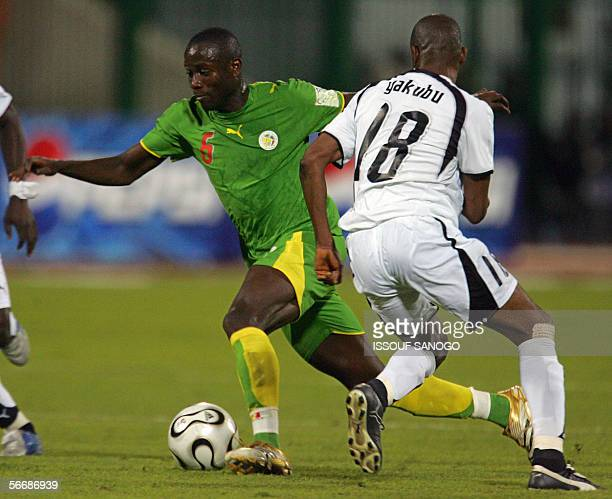 Senegalese Barry Rahmane player in L'Orient runs with the ball past Ghanaian Abubakari Yakubu during the knockout round game between Ghana's Black...