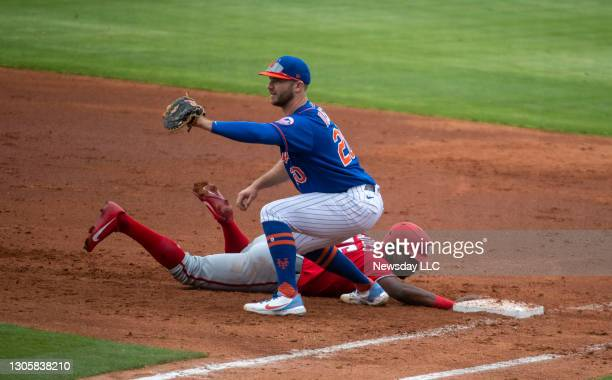 Washington Nationals' Victor Robles is safe at first base as New York Mets' Pete Alonso tries to tag him out in the third inning of a spring training...