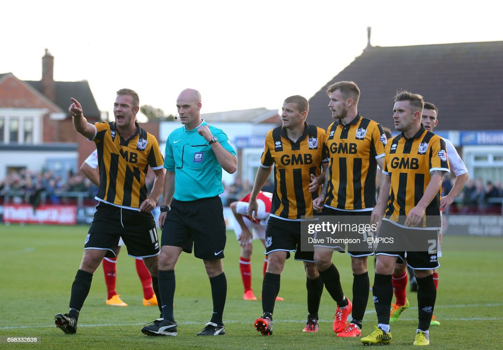 Port Vale players surround referee Kevin Johnson after he
