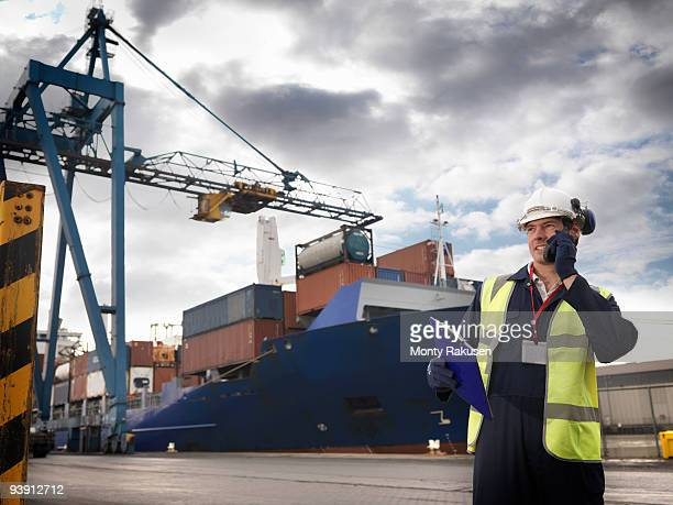 Port Worker In Front Of Loaded Ship