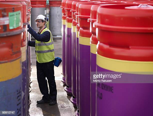port worker inspecting containers - monty rakusen stock pictures, royalty-free photos & images