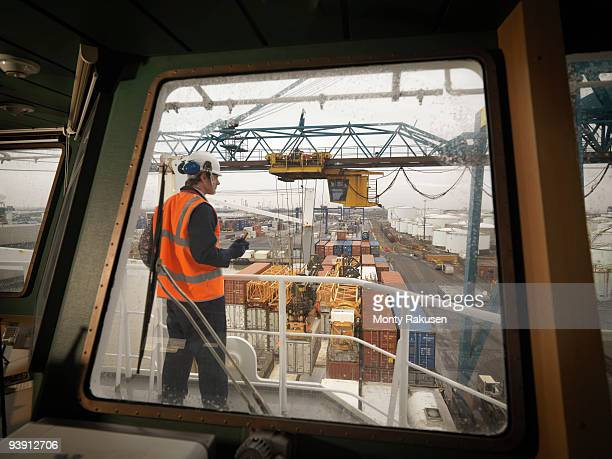 Port Worker Overseeing Loading Of Ship