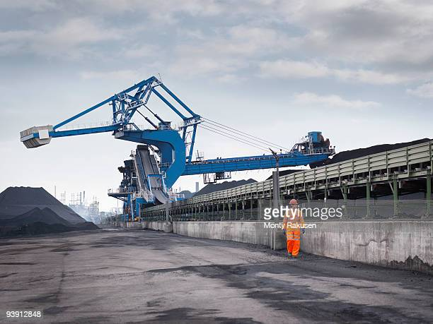 port worker with heavy machinery - monty rakusen stock pictures, royalty-free photos & images