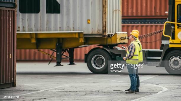 havenarbeiders die permanent op de terminal - beschermende werkkleding stockfoto's en -beelden