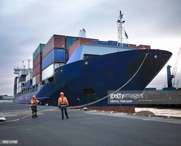 port workers with loaded ship at port - transport nautique photos et images de collection