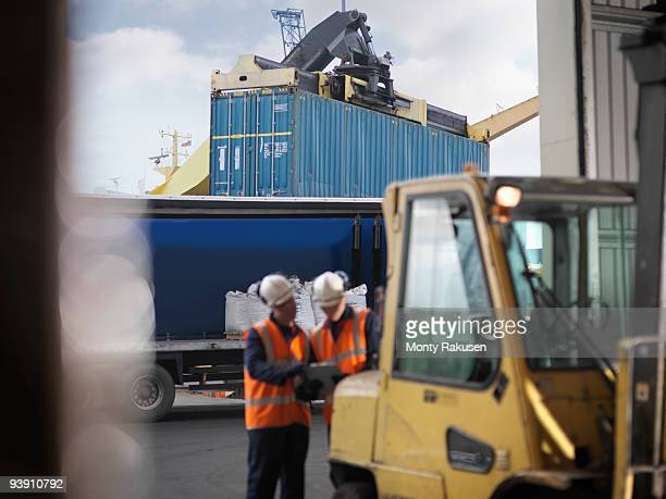 port workers with shipping container - loader reading stock pictures, royalty-free photos & images