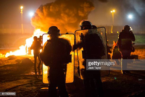 A portable chemical toilet burns as French riot police advance towards the Jungle migrant camp during a clash with migrants on October 23 2016 in...