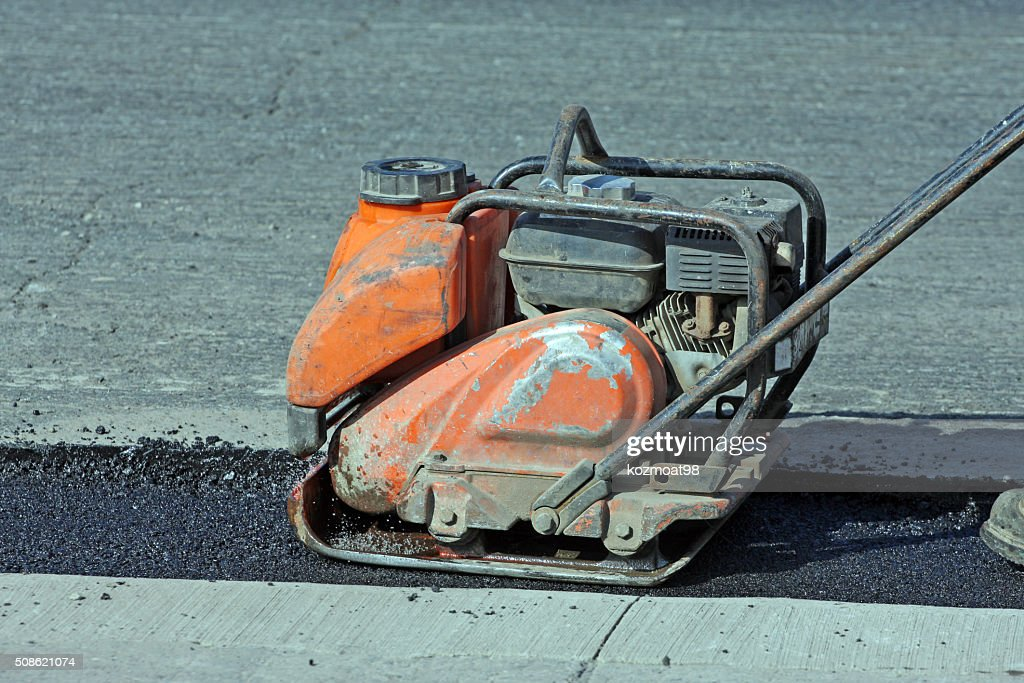 Portable Construction Compactor Compacting Asphalt On A Road Repair Site : Stock Photo