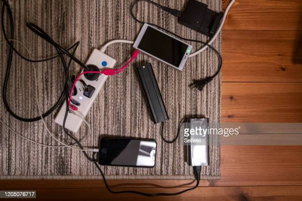 portable devices charing by the extension - power supply stock pictures, royalty-free photos & images