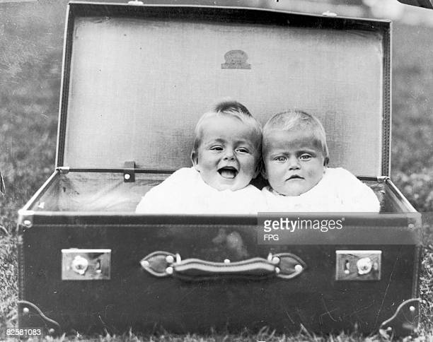Two babies packed into a large suitcase, circa 1930.