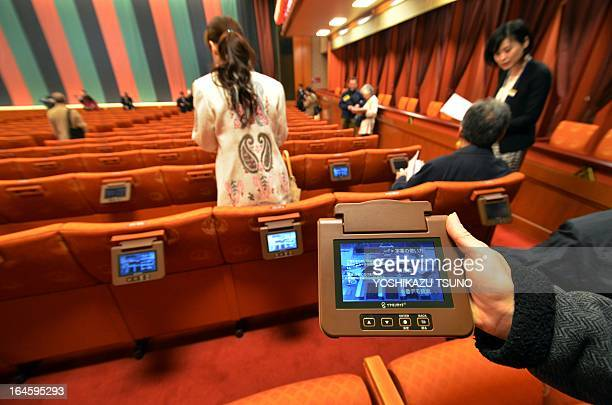 A portable monitors to read subtitles and other information for visitors is held for a picture at the recently rebuilt kabuki art theatre in Tokyo on...