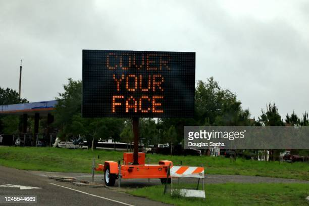 portable roadway sign warning people to cover your face to prevent covid-19 spreading - portable information device imagens e fotografias de stock