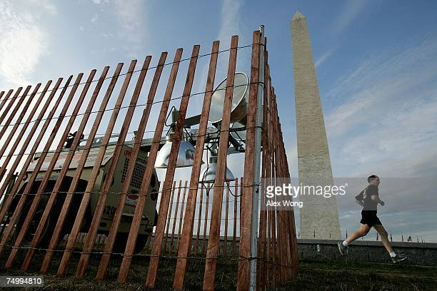 A portable spot lights is placed in position as a jogger runs by on the ground of Washington Monument July 3 2007 in Washington DC Preparation for...