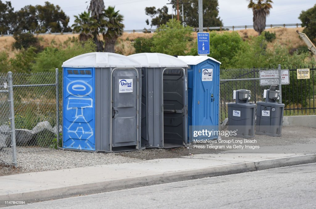 Portable toilets and sinks across from a homeless encampment on