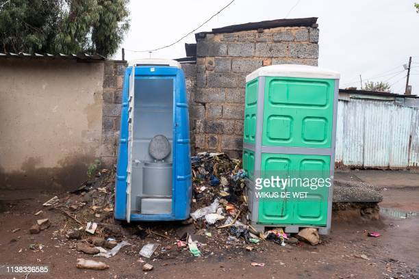 Portable toilets are photographed in an alley way between houses on April 5 2019 in Kliptown near Soweto South Africa goes to the polls next month...