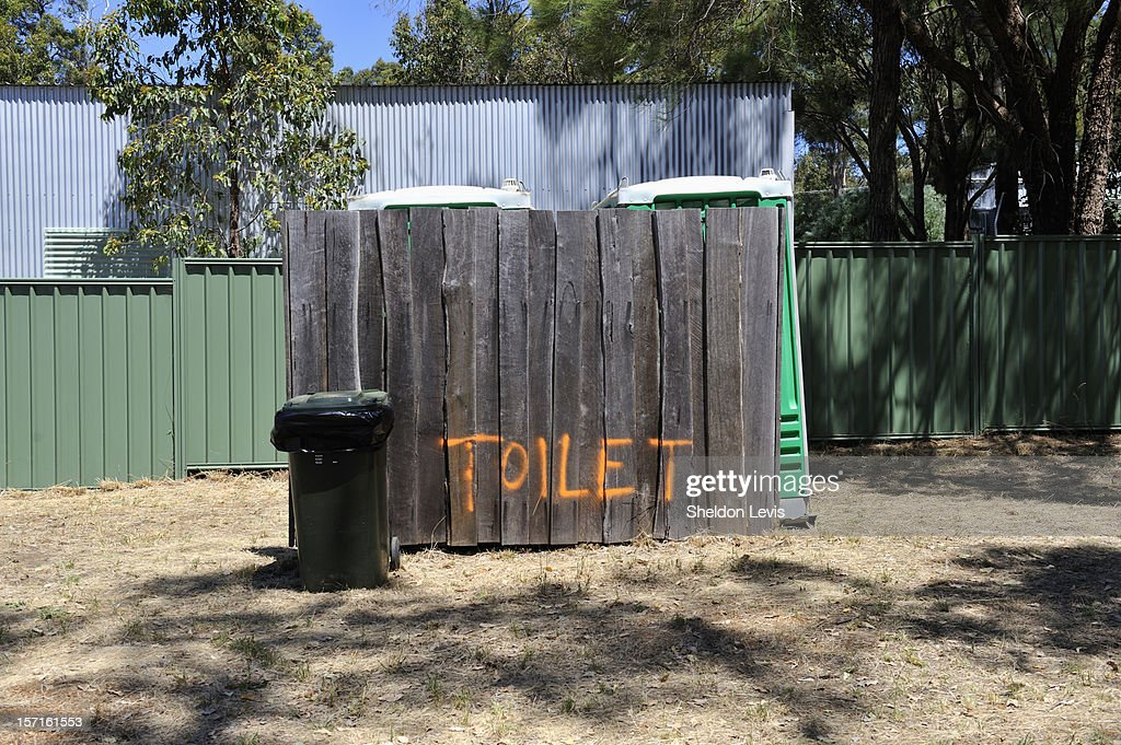 Portable toilets behind wooden, hand painted fence : Stock Photo