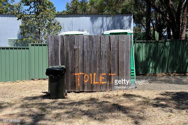 Portable toilets behind wooden, hand painted fence