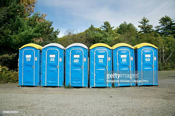 portable toilets in rural setting - portable toilet stock photos and pictures