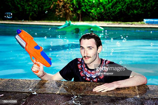 Portaint of male teenager in Pool with water gun