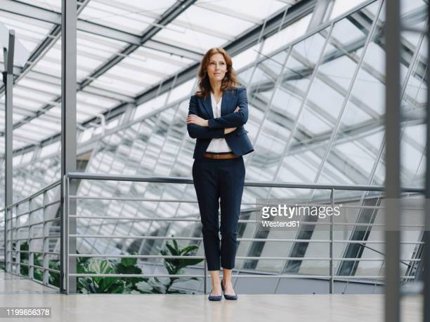 portait of a confident businesswoman in a modern office building - ganzkörperansicht stock-fotos und bilder