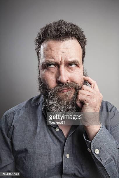Portait of a mature man scratching his full beard