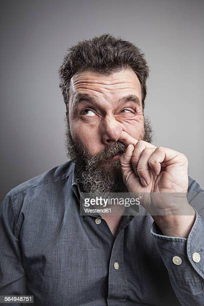 Portait of a mature man with full beard, picking his nose