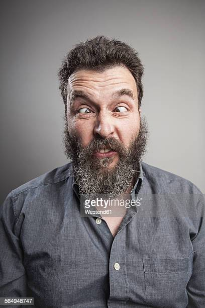 Portait of a mature man with full beard pulling faces