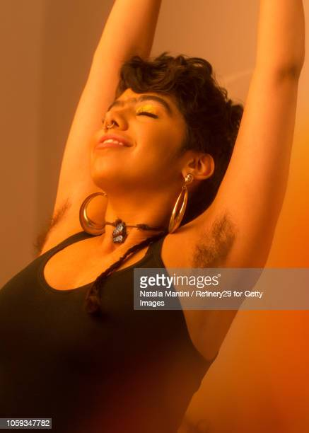 portait of a young latin american woman smiling - armpit hair stock-fotos und bilder