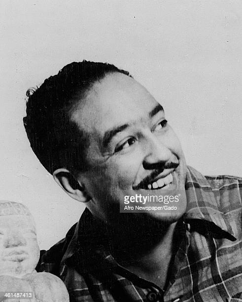 Portait of African American poet Langston Hughes with a statue, 1955.