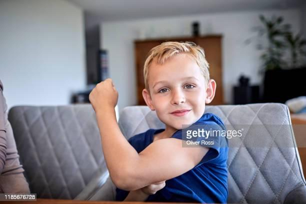 portait of boy flexing muscles at home - gender role fotografías e imágenes de stock