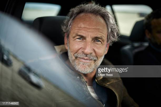 portait of confident man with grey hair in a car - mature men stock pictures, royalty-free photos & images