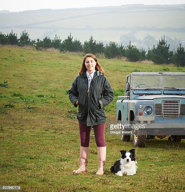 Portait of female farmer with dog and vehicle.