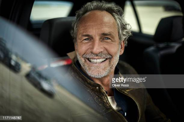 portait of happy man with grey hair in a car - satisfaction stock pictures, royalty-free photos & images