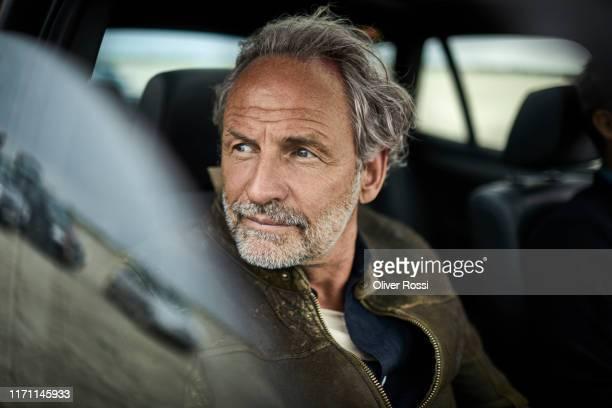 portait of man with grey hair in a car - fahren stock-fotos und bilder