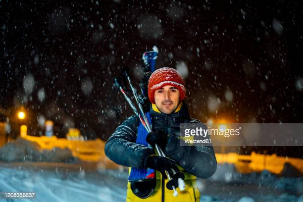 portait of man with skis in snowfall at night - sport d'hiver photos et images de collection
