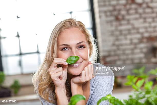 Portait of smiling blond woman holding basil leaf