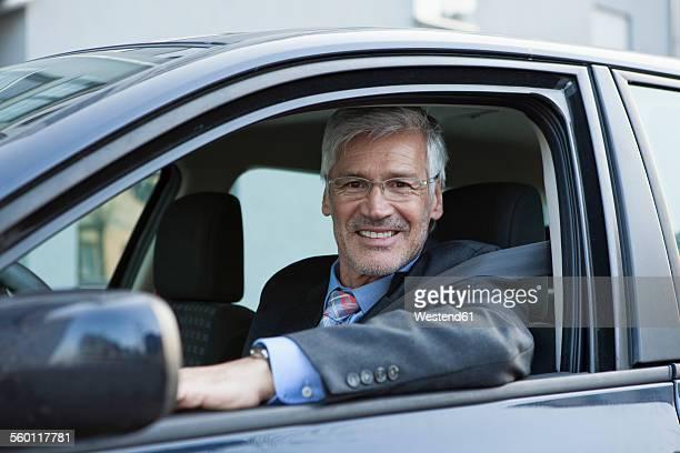 portait of smiling businessman sitting in his car - un seul homme d'âge mûr photos et images de collection